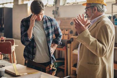Mature inspector scolding young carpenter in a repair shop.